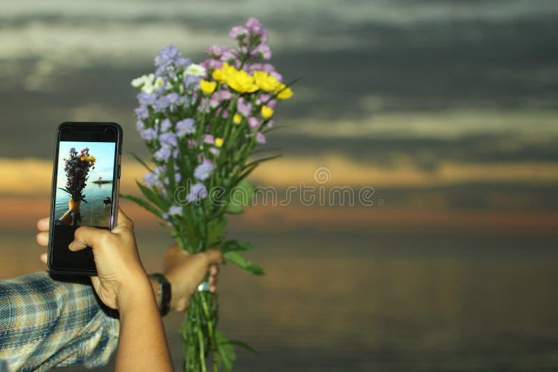 在手中夺取美丽的花花束由有黑智能手机的另一只手,多任务手 模糊的天空颜色和 免版税图库摄影