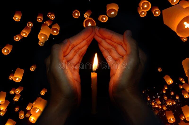 在手中对光检查光与浮动灯笼在夜空背景中 图库摄影