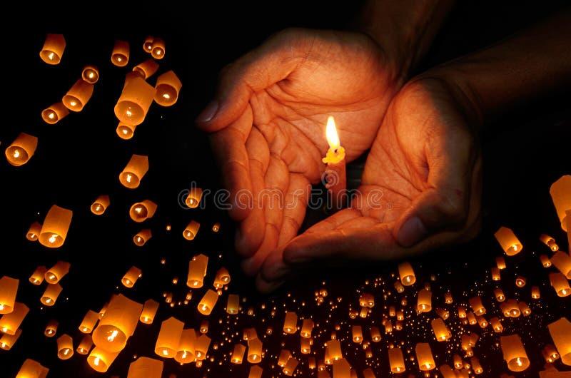 在手中对光检查光与浮动灯笼在夜空背景中 免版税库存图片