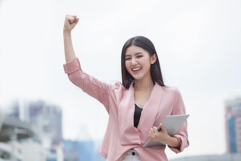 在手中庆祝的成功的亚洲女商人胳膊与片剂计算机在城市户外 女孩激动的优胜者 快乐, 免版税库存图片