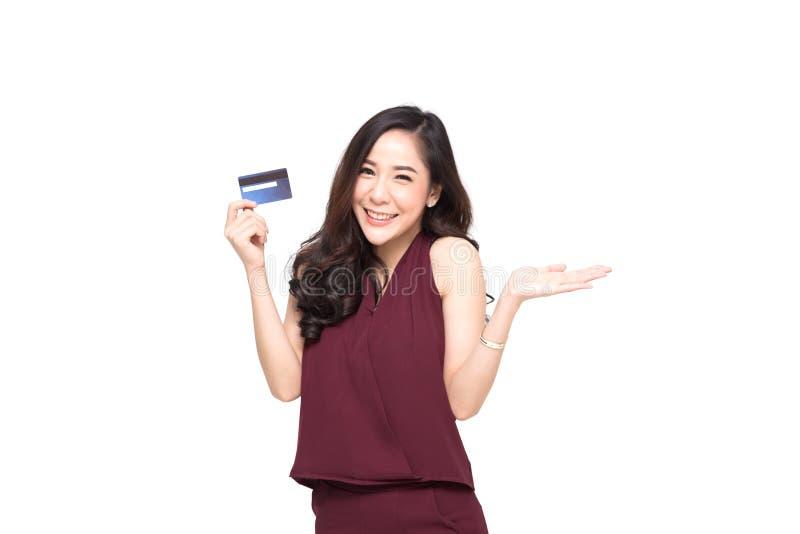 在手中当前信用卡做的年轻微笑的美丽的亚裔妇女付款购物 库存照片