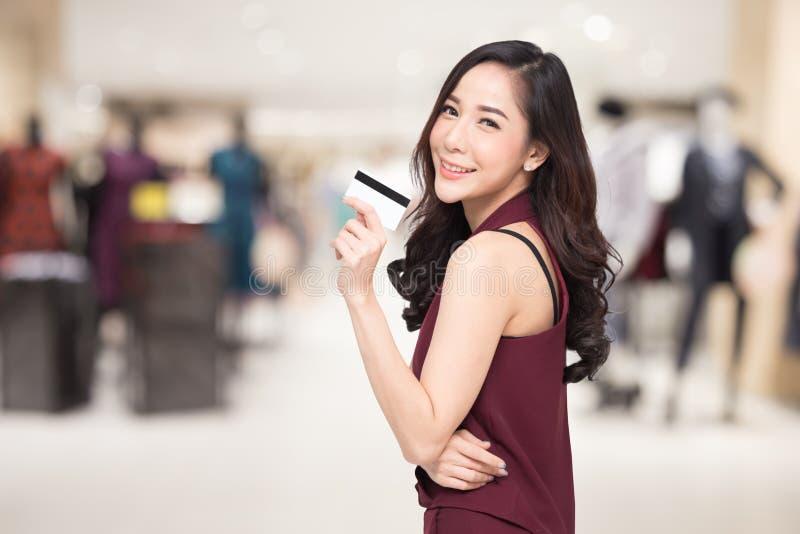 在手中当前信用卡在被弄脏的购物中心背景的微笑的美丽的亚裔妇女 免版税图库摄影