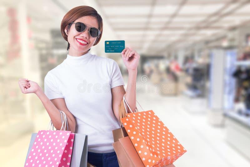 在手中当前信用卡的年轻美丽的亚裔妇女 免版税库存照片