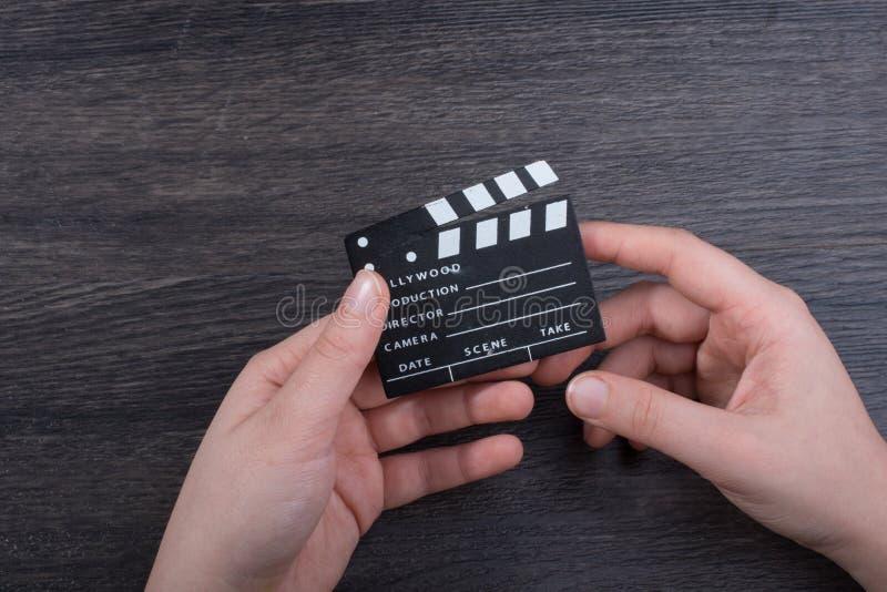 在手中拿着一个小的电影拍板的手 图库摄影