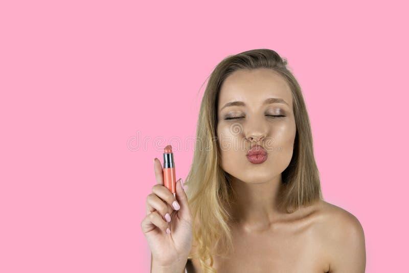 在手中拿着唇膏被隔绝的桃红色背景的女孩 免版税库存照片