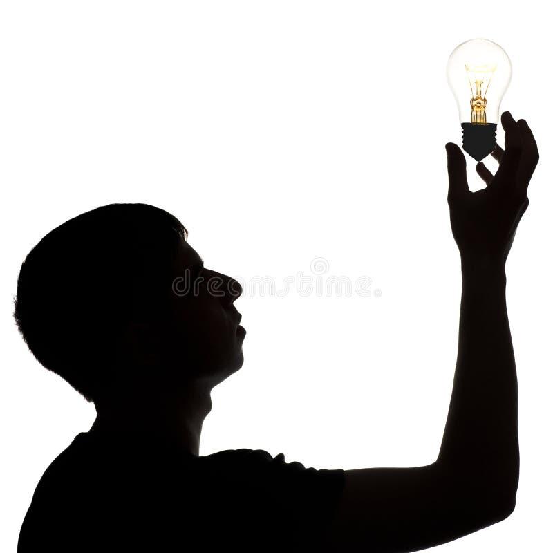在手中拿着白炽辉光灯的体贴的人剪影向上,想法电灯泡,想法的概念在白色孤立的 免版税库存照片