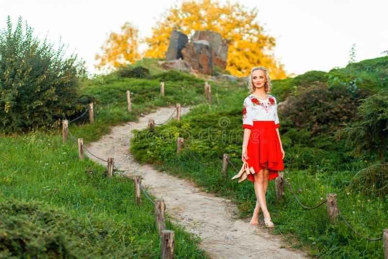 在手中拿着鞋子和走在道路的时髦的红色白色礼服的美丽的赤足妇女在小山 站立在路村庄 免版税库存照片