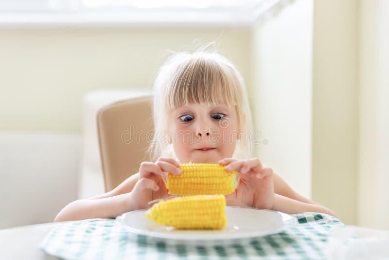 在手中拿着鲜美煮沸的甜玉米玉米棒和lokking对此的逗人喜爱的白肤金发的白种人女孩与惊奇宽被张开的眼睛 儿童爱 库存图片