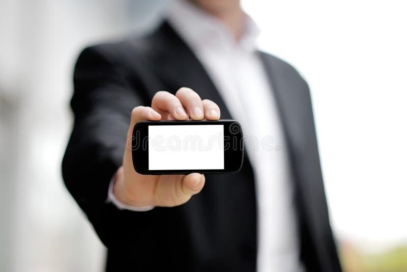 在手中显示黑流动巧妙的电话的商人 库存图片