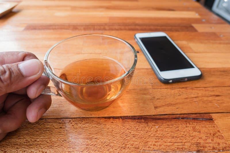 在手中杯热的茶并且打电话在木桌背景 图库摄影