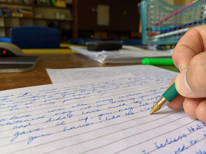 在手中标记检查纸的老师在有绿色笔的一张书桌 免版税库存照片