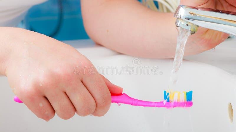 在手中牙刷的牙膏,在卫生间水槽 图库摄影