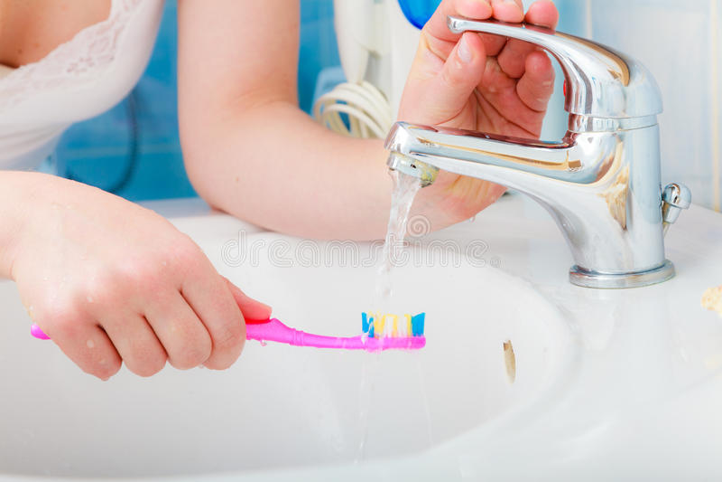 在手中牙刷的牙膏,在卫生间水槽 库存图片