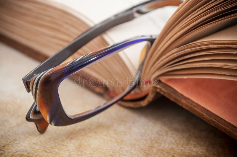 在手中玻璃在古老书开放在木桌上 库存图片