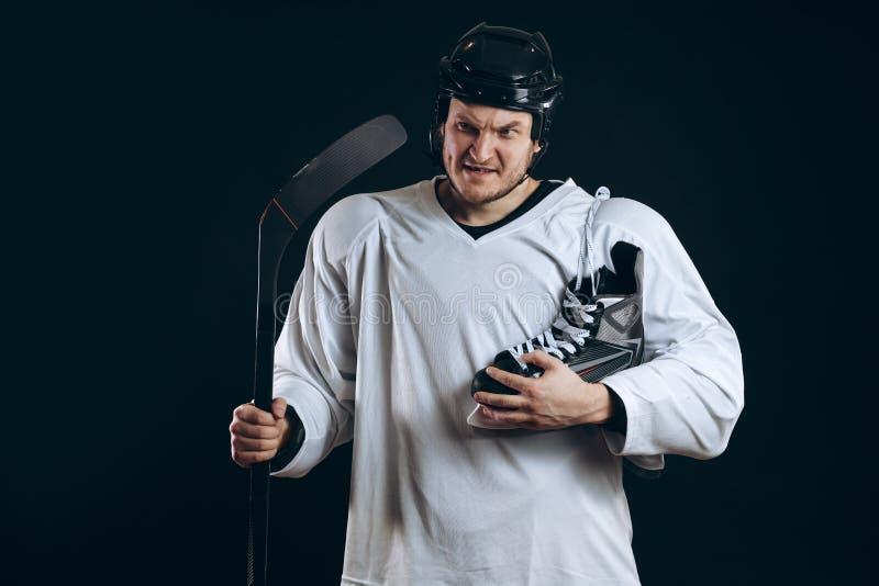 在手中看与冰鞋的确信的曲棍球运动员照相机 查出在黑色 免版税库存照片