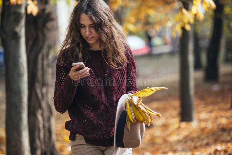 在手中看她的手机智能手机在秋天的妇女户外 惊奇的女孩在秋天森林里 图库摄影