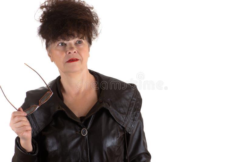 戴在手中眼镜的惊奇的成熟妇女 免版税库存照片