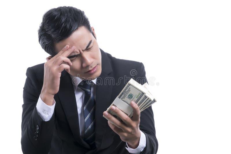 在手中考虑金钱的年轻商人画象 免版税库存照片