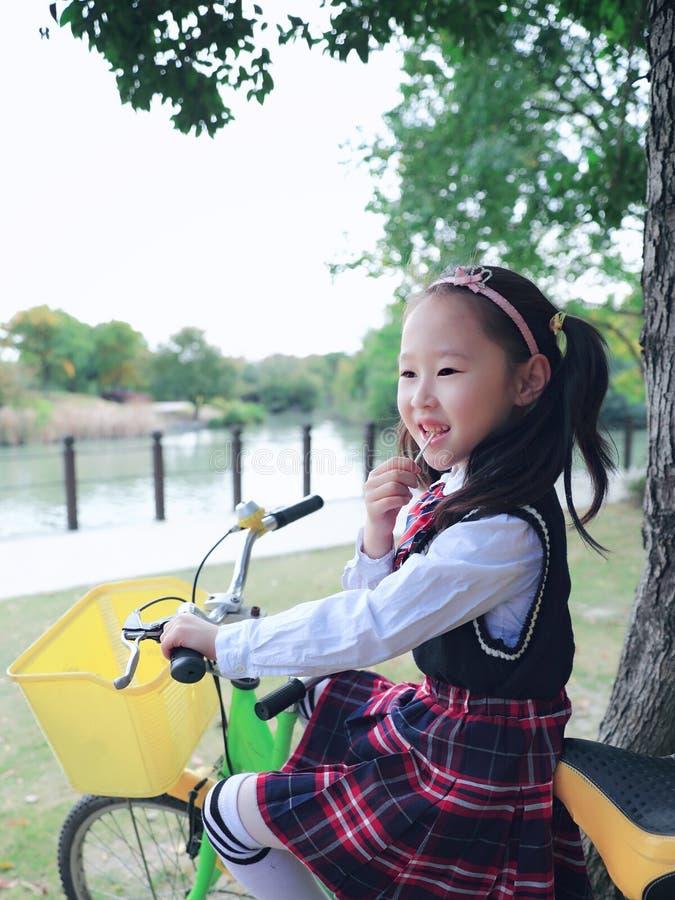 在手中说谎在网络自行车的小女孩在公园ï ¼ ŒWith棒棒糖 图库摄影