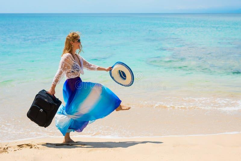 在手中走在带着手提箱的海滩的妇女 免版税图库摄影