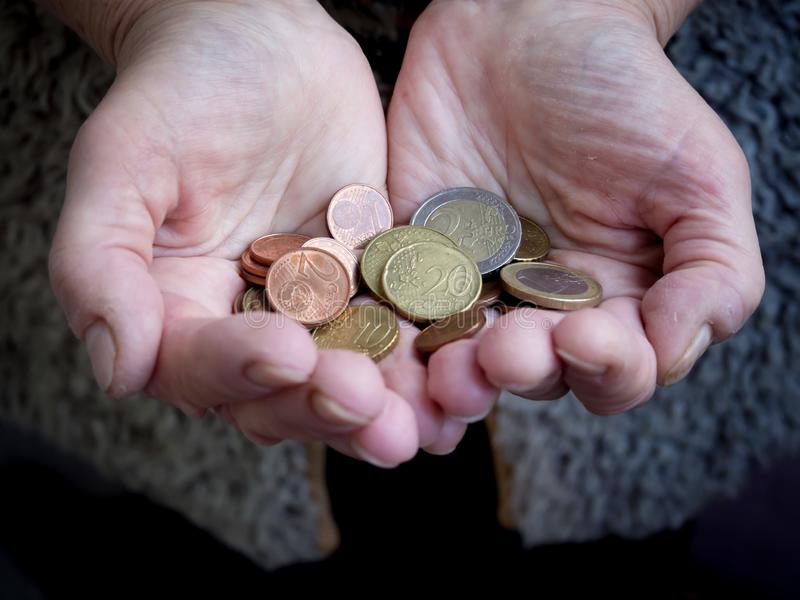 在手中退休与硬币 贫穷的问题 免版税图库摄影