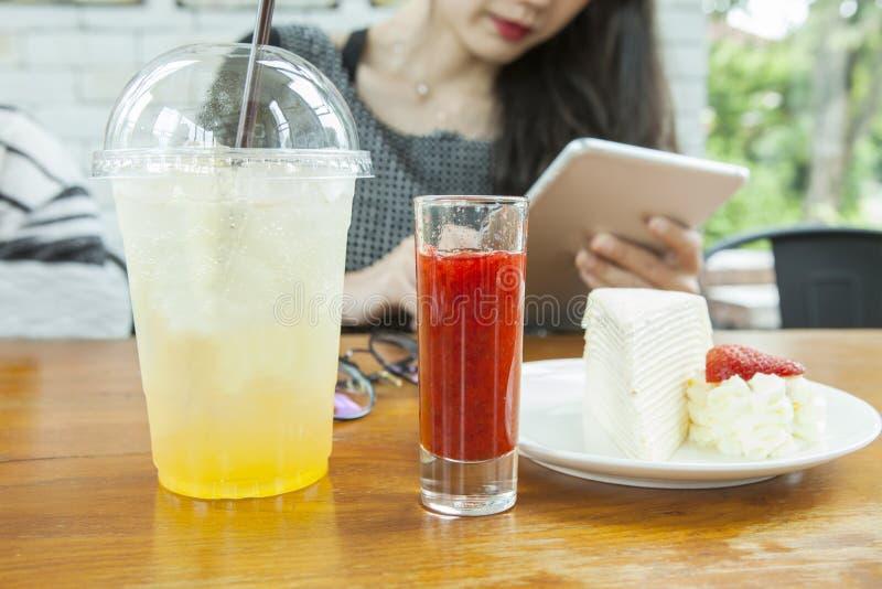 在手中选址在与巧妙的垫和strawbery绉纱蛋糕的木桌上的妇女立即可食在桌上 免版税库存图片