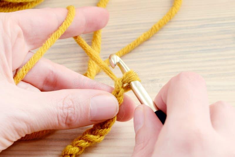 在手中钩编编织物与棕色羊毛 库存照片