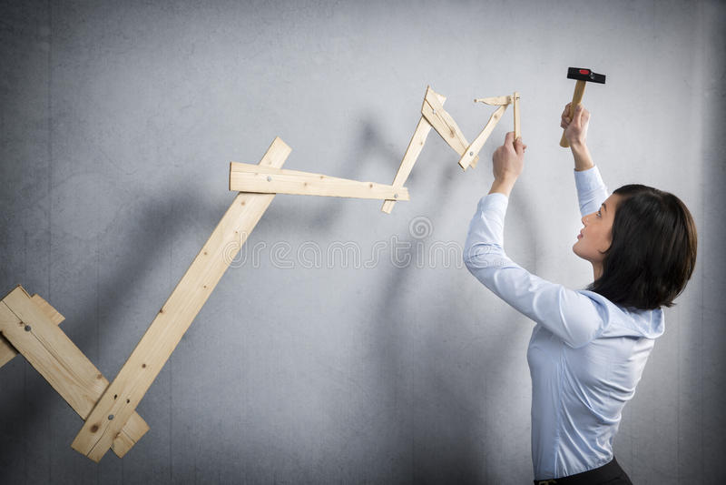 在手中建立与锤子的确信的妇女正面趋向图表 免版税库存图片