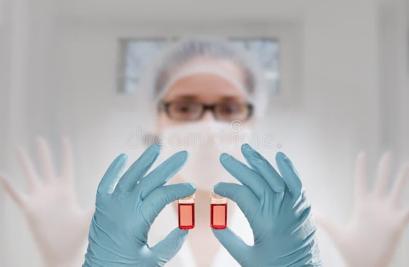 在手套的两只手拿着在技术前面的两个液体样品 库存图片
