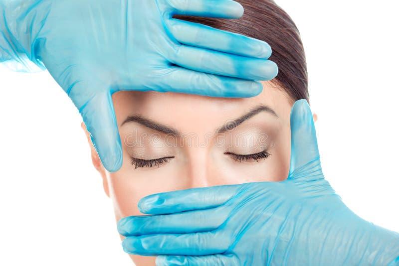 在手套的医生的手在女孩的眼睛附近 免版税图库摄影