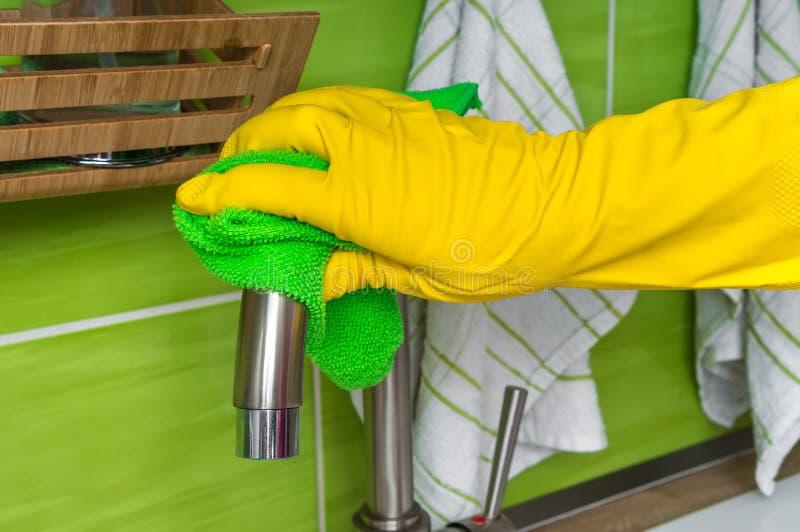 在手套的手与绿色旧布在厨房里抹龙头 库存照片