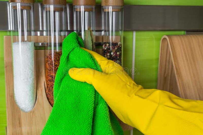 在手套的手与绿色旧布抹香料瓶 库存图片