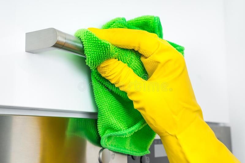 在手套的手与绿色旧布清洗不锈钢把柄 免版税图库摄影