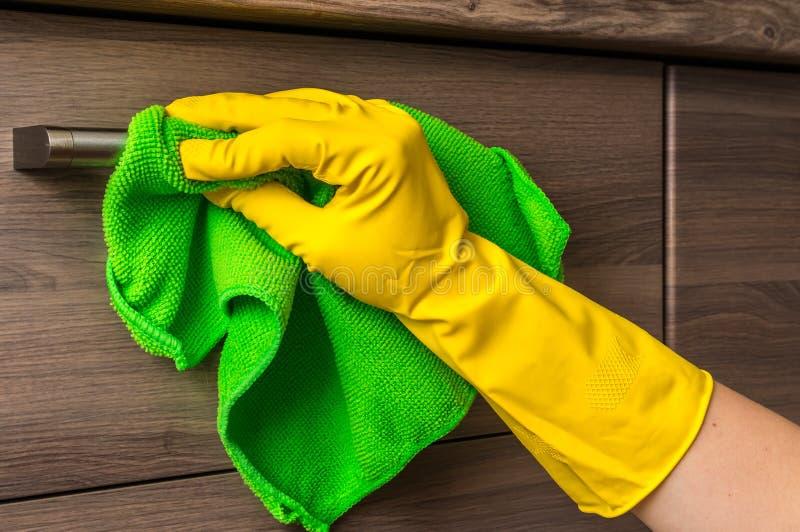在手套的手与绿色旧布清洗不锈钢把柄 库存图片