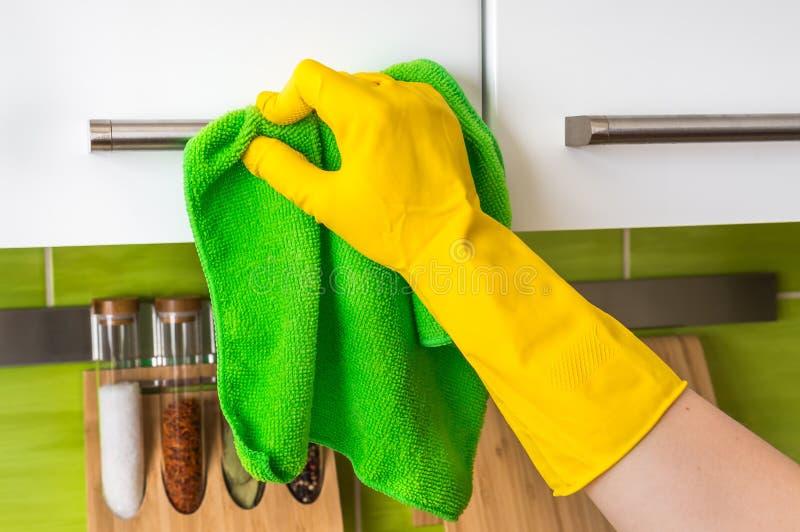 在手套的手与绿色旧布清洗不锈钢把柄 免版税库存图片
