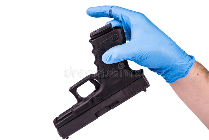在手套的手保留手枪 免版税库存图片