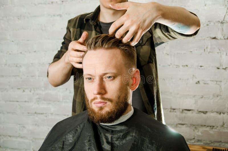 在手套的理发师手剪了称呼成人砖墙背景的头发和头发gihger有胡子的人 人的接近的画象 库存照片