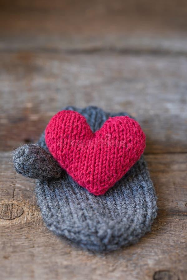 在手工制造露指手套的被编织的红色心脏,华伦泰` s天明信片 免版税库存图片