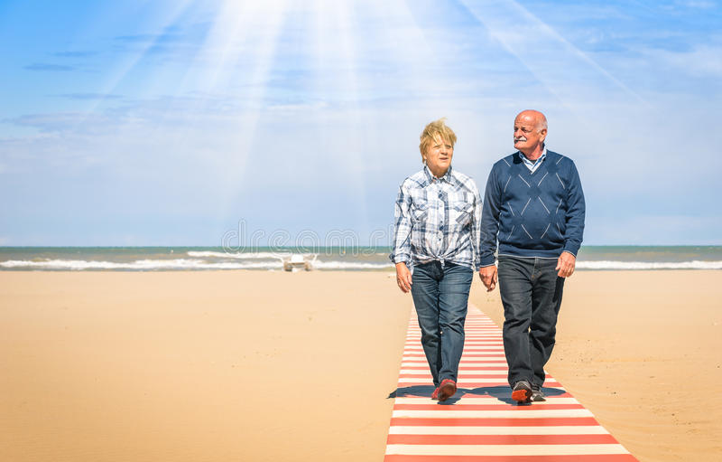 在手拉手走在海滩的爱的愉快的资深夫妇 图库摄影