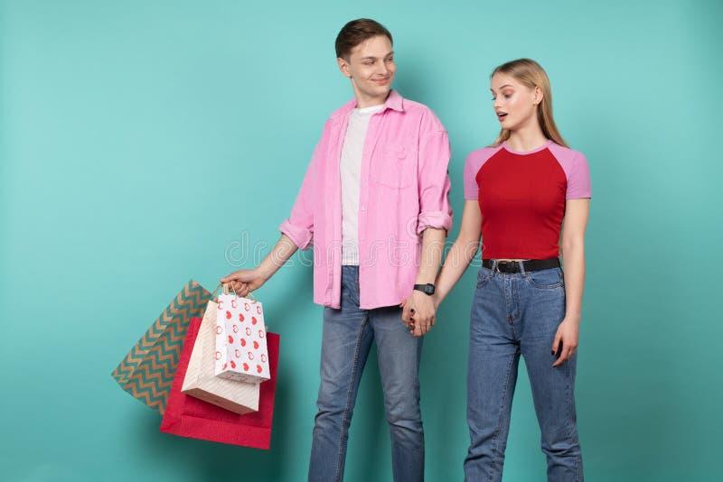 在手拉手wallking在一起购物以后的便衣的年轻浪漫夫妇 免版税库存图片