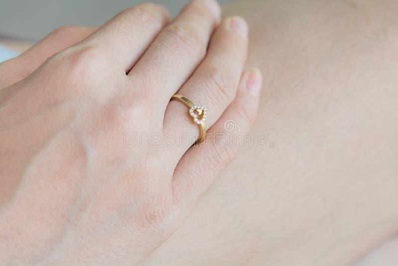在手指的一个心形的圆环 图库摄影