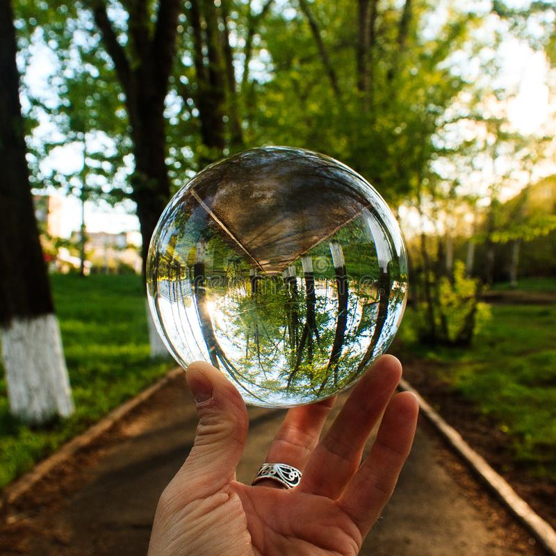 在手指的大透明玻璃球在室外背景打翻的武器储备 图库摄影
