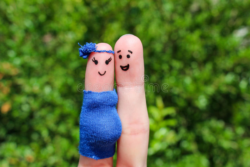 在手指绘的面孔 愉快的夫妇,妇女怀孕 免版税库存图片