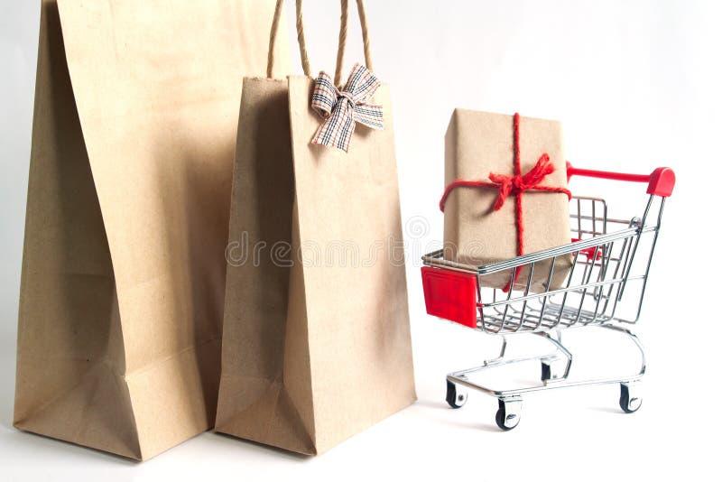 在手推车和购物带来的礼物盒在白色背景 免版税库存图片