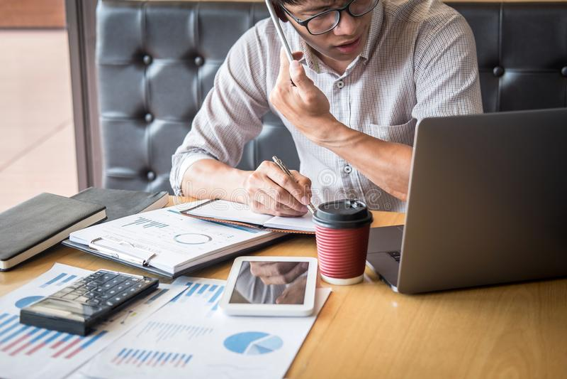在手提电脑的商人运作的投资方案有报告文件的和分析,计算关于图表的财务数据 图库摄影