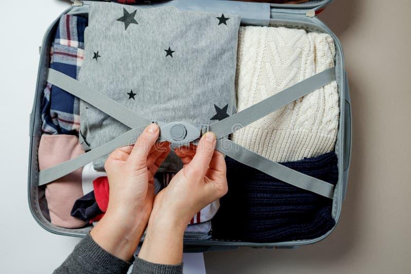在手提箱的妇女手被包装的衣裳 冬天假期和hol 库存图片