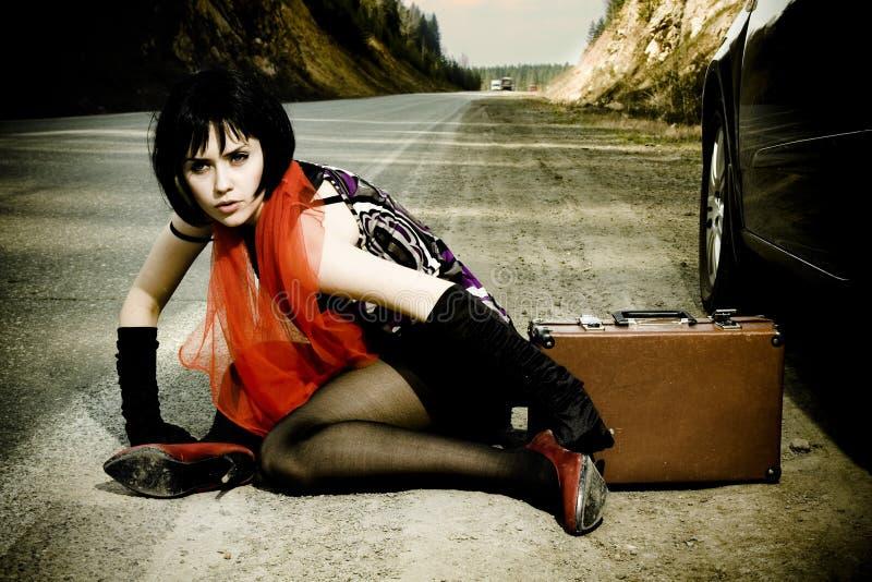 在手提箱附近的可爱的汽车女孩 库存图片