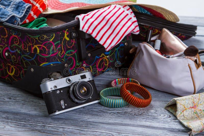 在手提箱附近的照相机有衣裳的 库存照片