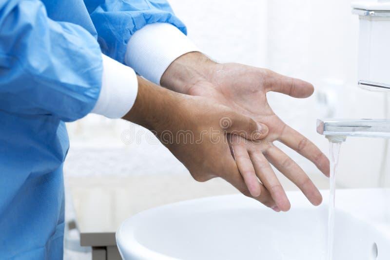 在手术前的外科医生洗涤的手 免版税库存图片