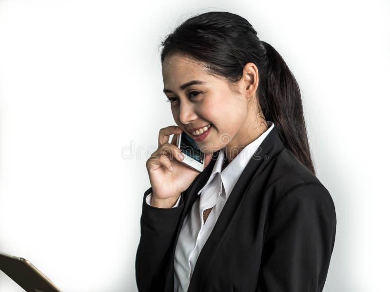 在手机和举行片剂的亚洲秀丽女商人闲谈在白色背景 免版税图库摄影